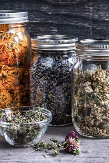 formulating herbal remedies with dried herbs in apothecary jars based on list of herbal actions